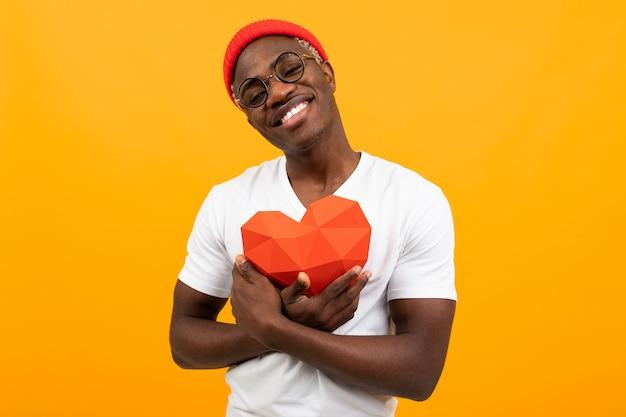 L'americano bello sveglio in maglietta bianca tiene il cuore 3d fatto di carta per il giorno di biglietti di s. valentino su fondo giallo