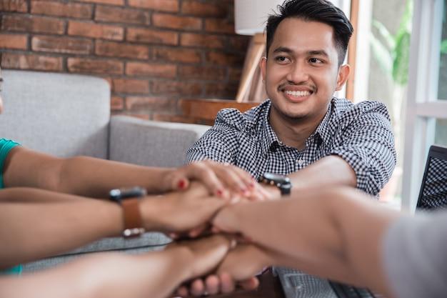L'amico asiatico del college stringe la mano insieme