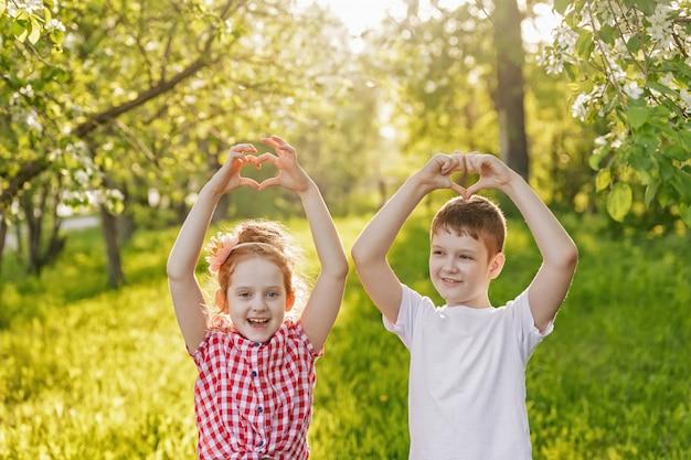 L'amico bambino ha piegato le sue mani a forma di cuore.