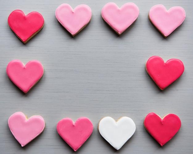 L'amore decorativo di forma dei cuori variopinti del biscotto modella lo spazio designato del biglietto di s. valentino