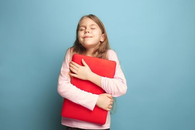 L'amore per il computer. ragazza teenager con il taccuino su un blu.