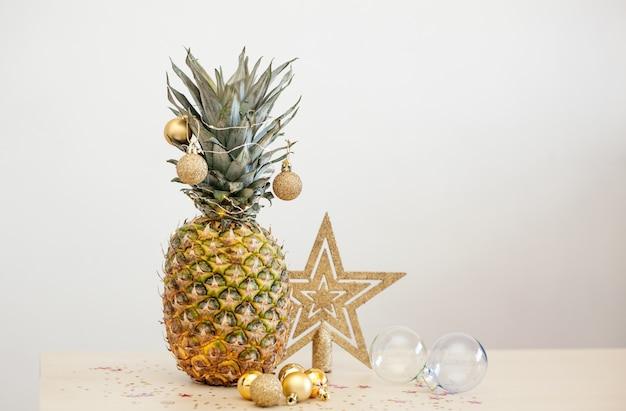 L'ananas ha decorato con le sfere dorate di natale su bianco
