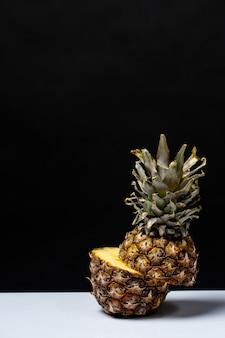 L'ananas ha tagliato a metà su una tabella sul nero