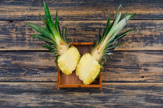 L'ananas maturo ha tagliato a metà in un piatto di legno sul vecchio lerciume di legno, vista superiore.