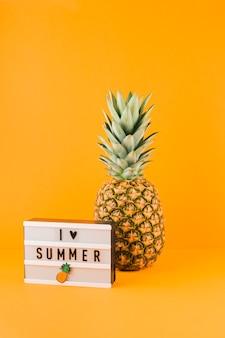 L'ananas vicino alla scatola leggera con la parola amo l'estate contro il contesto giallo