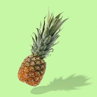 L'ananas vola nell'aria sul layout creativo luminoso, copia spazio