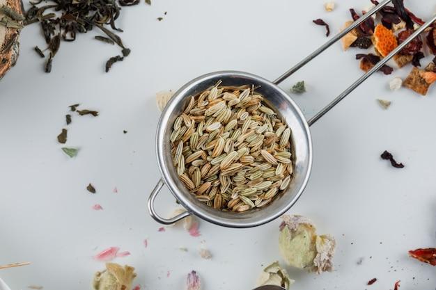 L'anice in un piccolo setaccio con il tè essiccato piatto giaceva su una superficie bianca