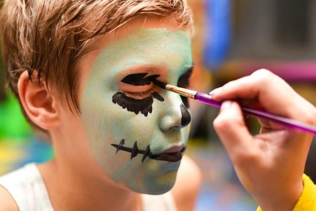 L'animatore dipinge il viso del bambino
