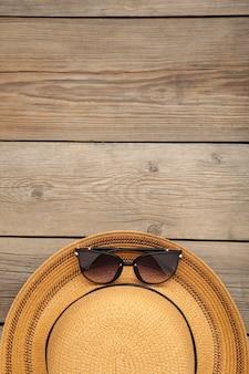 L'annata fabbrica il cappello e gli occhiali da sole di paglia su fondo di legno grigio.