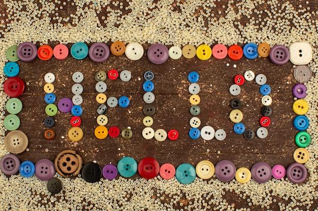 L'annata variopinta dei bottoni per il cucito ciao la parola ha modellato intorno ai piccoli bottoni gialli su uno scrittorio rustico di legno