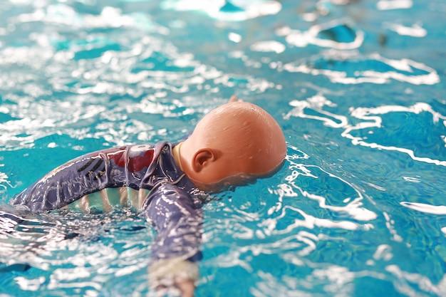 L'annegamento fittizio della bamboletta di addestramento galleggia nello stagno.