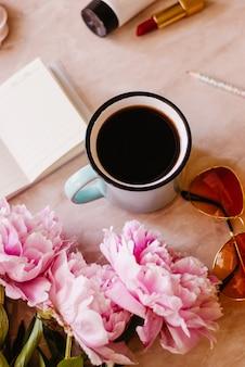 L'appartamento di bellezza giaceva con un diario, una tazza di caffè, accessori e peonie su uno sfondo di marmo