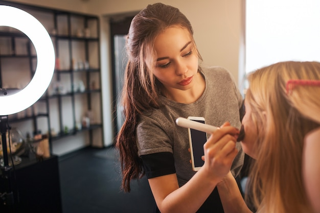 L'applicazione del giovane truccatore arrossisce sulle guance bionde della donna nella stanza di bellezza. sguardo professionale al cliente.