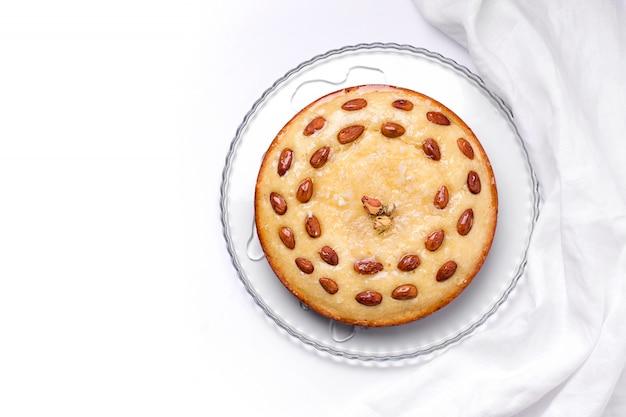 L'arabo tratta la torta basbus con semolino, cocco e mandorle su uno sfondo bianco