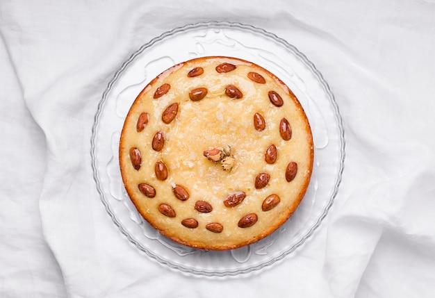L'arabo tratta la torta basbus su lino bianco