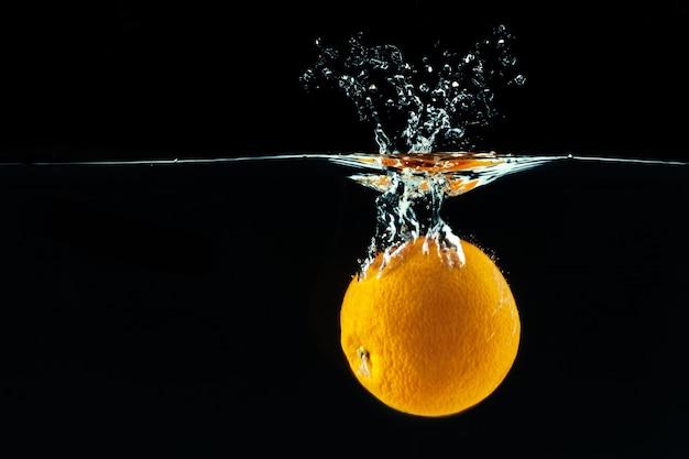 L'arancia cade nell'acqua e fa schizzi