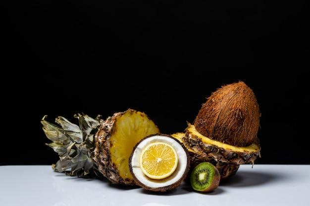 L'arancia e il kiwi della noce di cocco hanno tagliato a metà su una tavola sul nero