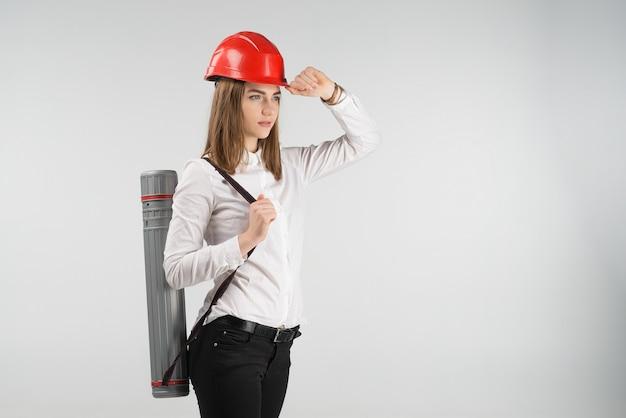 L'architetto donna si leva in piedi con un tubo dietro la sua parte posteriore tocca il casco arancione