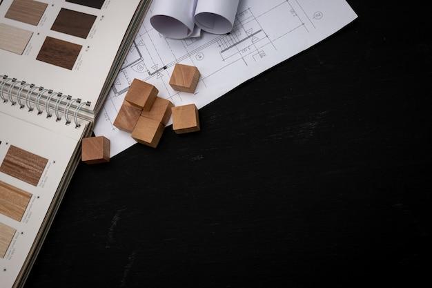 L'architetto ha progettato l'edificio nell'ufficio di progettazione, la pianta del pavimento con cataloghi di materiali decorativi e altri accessori sul tavolo di legno nero.