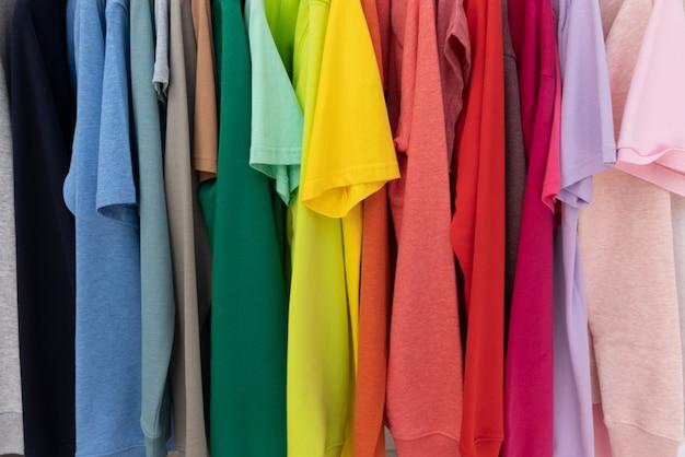 L'arcobaleno colora i vestiti sui ganci per fondo