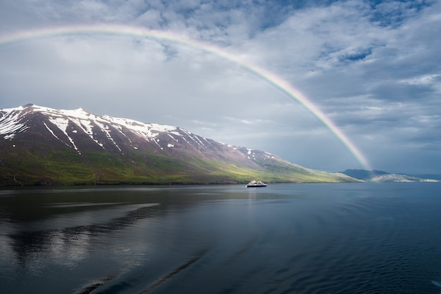 L'arcobaleno sul mare vicino alle montagne innevate e una nave isolata