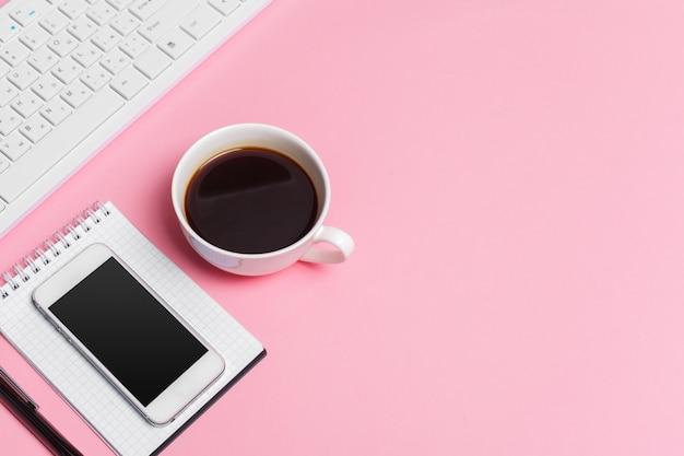 L'area di lavoro creativa rosa della donna con la tastiera e i rifornimenti di computer, vista superiore