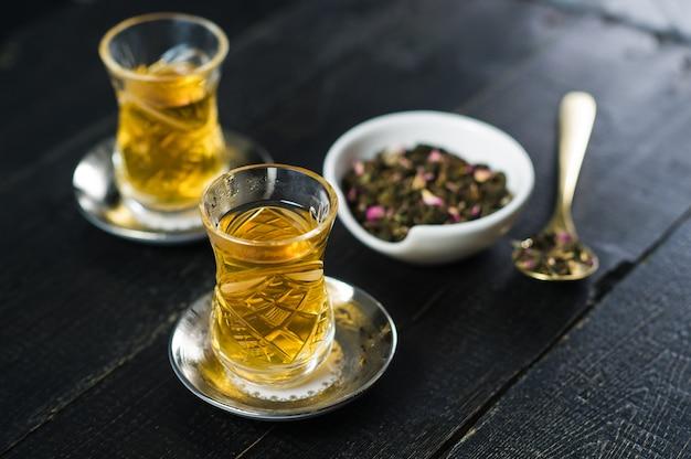 L'armud con il tè, la cerimonia del the. fondo in legno nero.