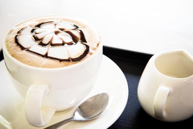 L'arte del caffè del latte si veste in su sulla crema molle della bolla pronta da bere sulla tavola