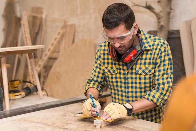 L'artigiano passa in guanti protettivi che misurano il blocco di legno con il righello e la matita