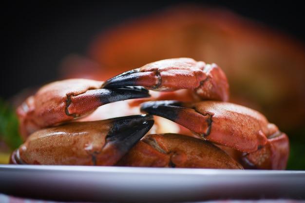 L'artiglio del granchio cucinato bollito sul piatto ha servito i frutti di mare vicini, granchi di pietra rossi