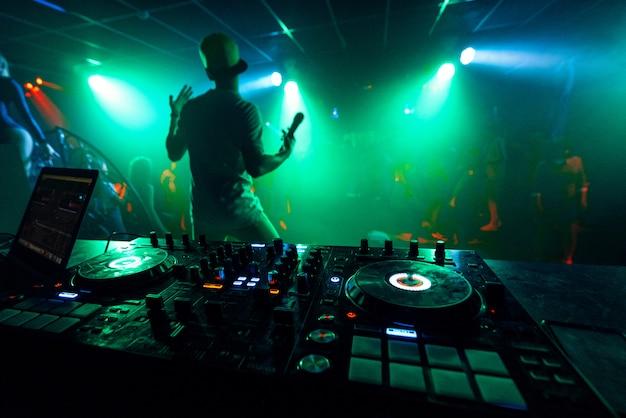 L'artista con un microfono si esibisce sul palco di una discoteca