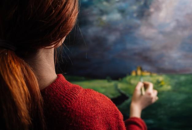 L'artista della donna dipinge un'immagine con un pennello su un cavalletto