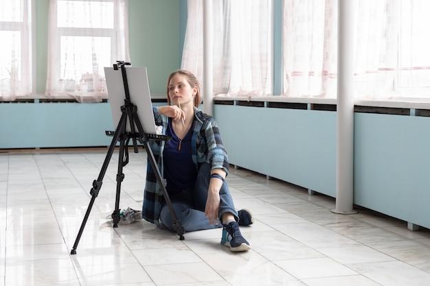 L'artista della giovane donna dell'adolescente dipinge con le pitture ad olio che si siedono sul pavimento di marmo. tela bianca e cavalletto si trovano sul pavimento di piastrelle di marmo nella stanza con pareti turchesi e verde chiaro.
