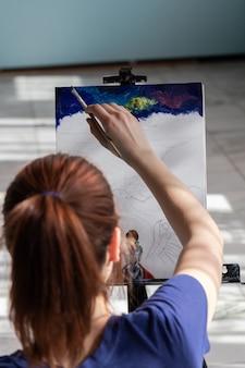 L'artista donna giovane adolescente è seduta sul pavimento di piastrelle di marmo. donna in procinto di dipingere con colori ad olio.