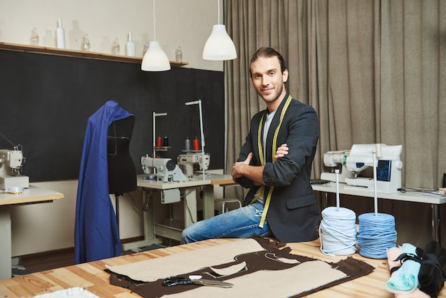 L'artista e il suo posto di lavoro. ritratto del progettista di vestiti maschio caucasico attraente maturo con l'acconciatura alla moda e l'attrezzatura alla moda che si siedono nel suo studio, posanti per la foto in rivista di moda.
