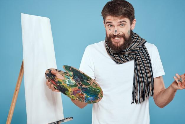 L'artista maschio dipinge un'immagine su tela con un cavalletto