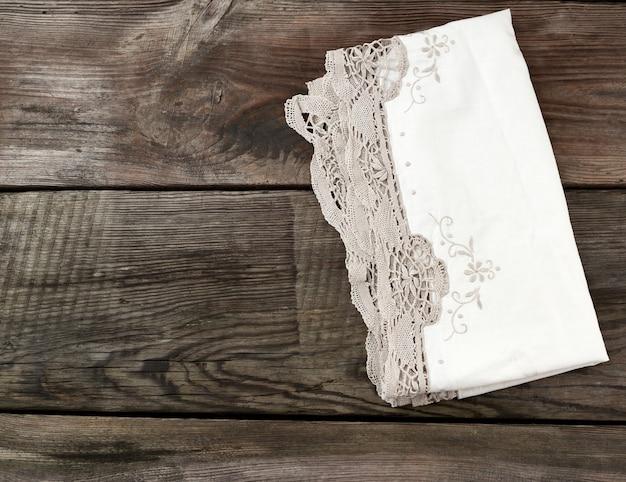L'asciugamano bianco del pizzo del tessuto della cucina ha piegato su una tavola di legno grigia