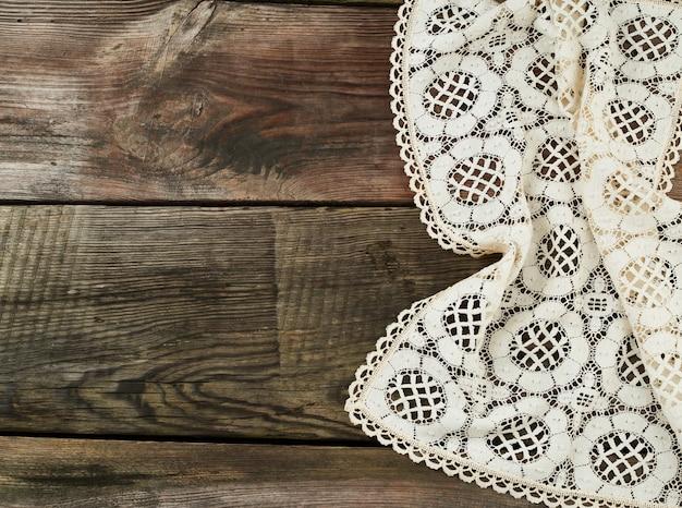 L'asciugamano bianco del tessuto della cucina ha piegato su una tavola di legno grigia
