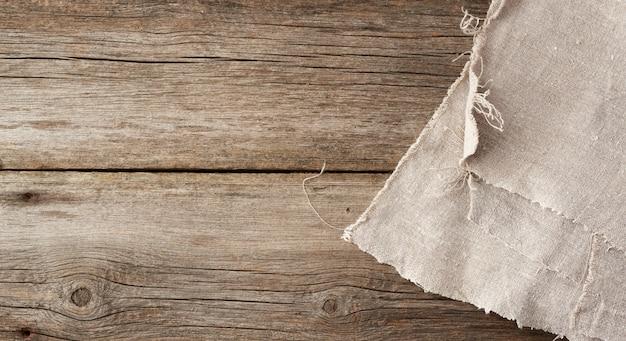 L'asciugamano grigio del tessuto della cucina ha piegato su una tavola di legno grigia dai bordi anziani, vista superiore
