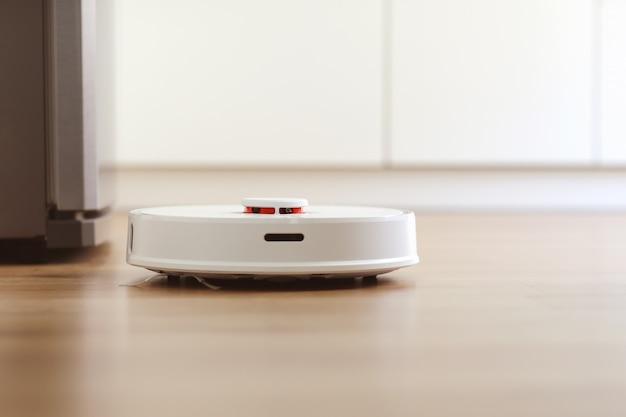 L'aspirapolvere robot bianco pulisce il pavimento