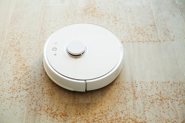 L'aspirapolvere robot esegue la pulizia automatica dell'appartamento in un determinato momento. casa intelligente.
