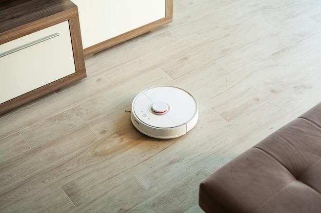 L'aspirapolvere robot esegue la pulizia automatica dell'appartamento in un determinato momento. casa intelligente