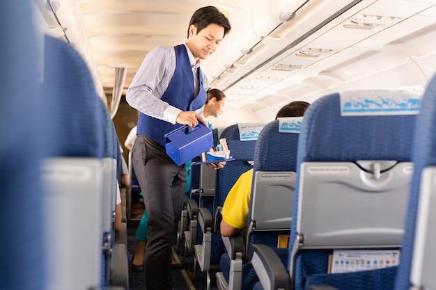 L'assistente di volo di bangkok airways serve da bere ai passeggeri a bordo.