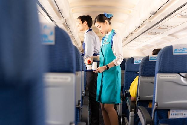 L'assistente di volo di bangkok airways serve da mangiare ai passeggeri a bordo.