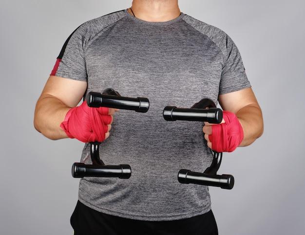 L'atleta adulto in una maglietta grigia è in piedi e in possesso di un simulatore sportivo