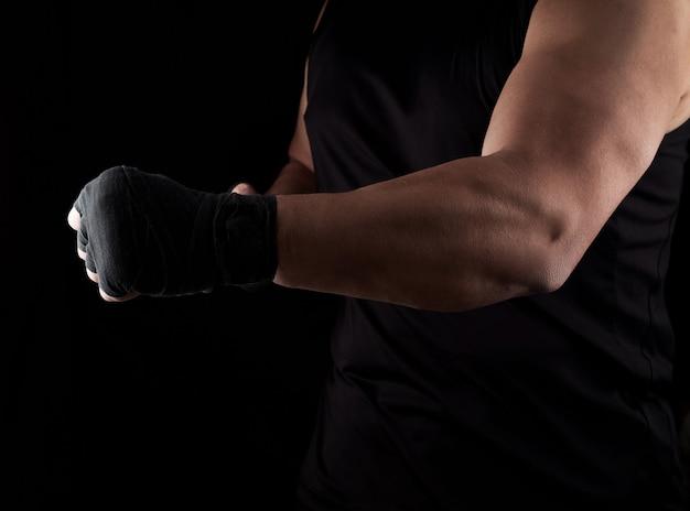 L'atleta adulto in uniforme nera sta stando in una cremagliera con i muscoli tesi