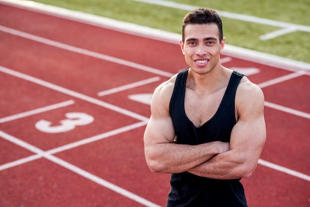 L'atleta bello sorridente in un'attrezzatura sportiva con le sue armi ha attraversato sulla pista di corsa che esamina la macchina fotografica