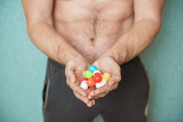 L'atleta bodybuilder prende la droga sotto forma di compresse sotto forma di farmaci rapidi progressi nello sviluppo muscolare