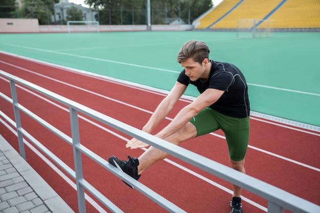 L'atleta dell'uomo fa l'allungamento degli esercizi all'aperto