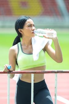 L'atleta della donna fa una pausa e beve l'acqua